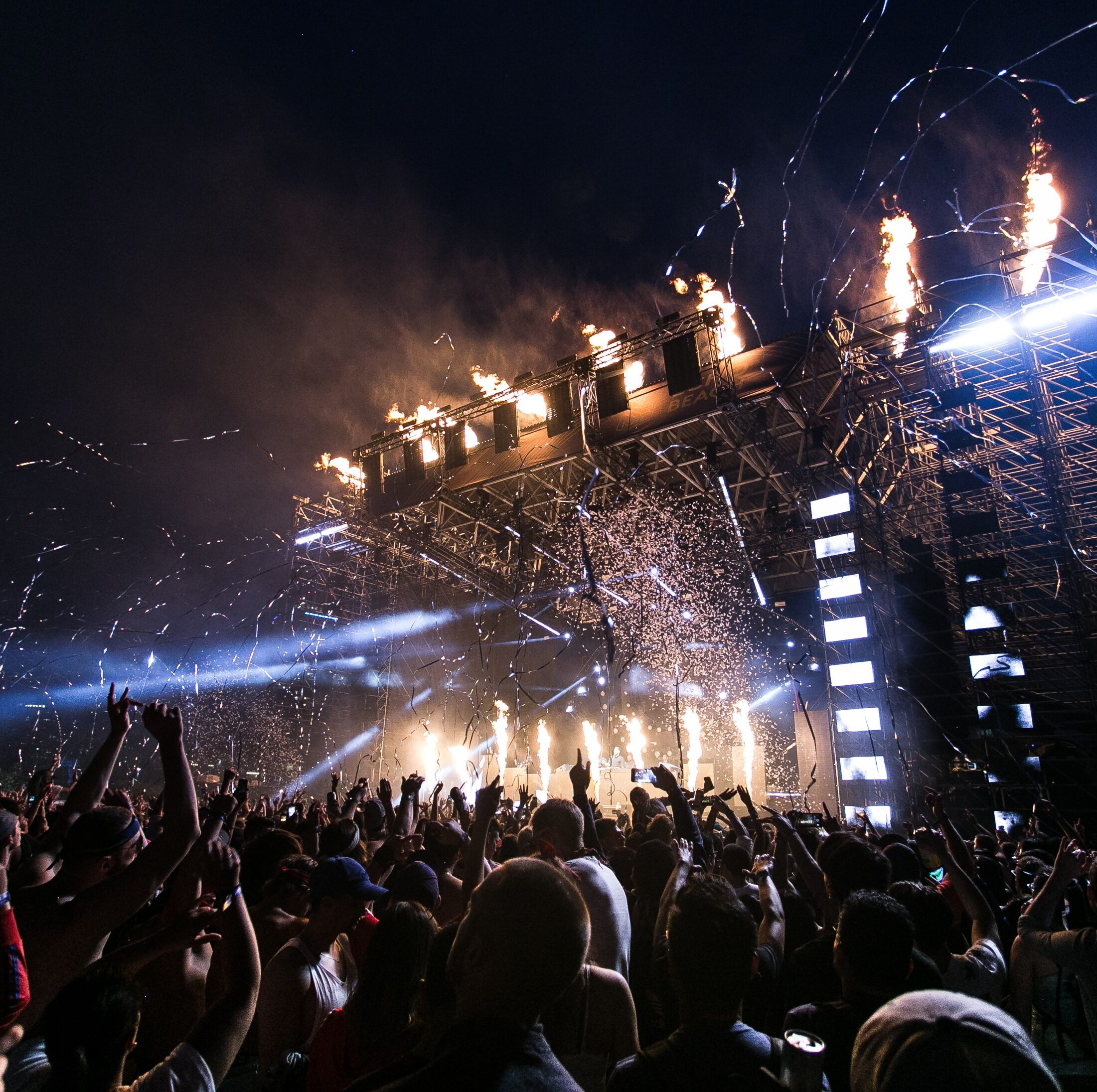 A crowd of people at a concert with flashing lights